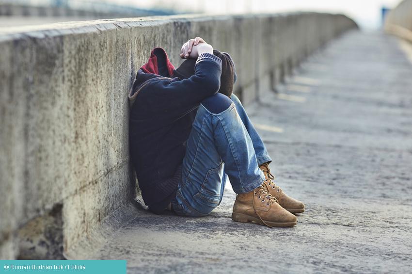 Junge sitzt an Brückenrand